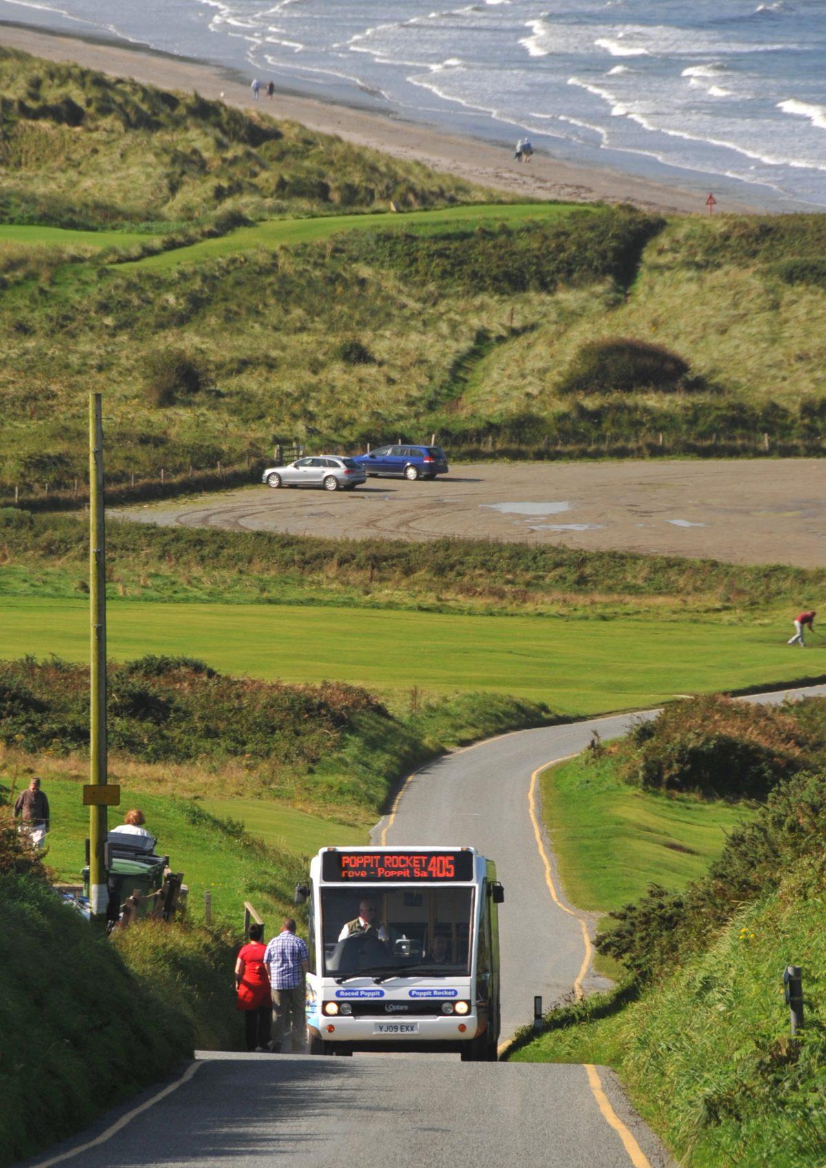 Bus picking up passengers on a narrow coastal road