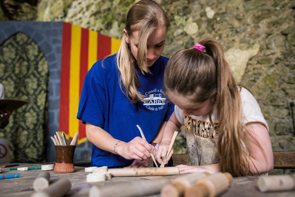 Two girls using a quill pen at Carew Castle