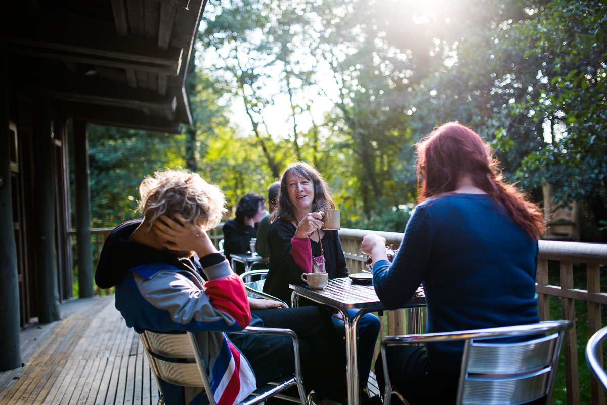 Visitors sit outside on the Castell Henllys cafe veranda