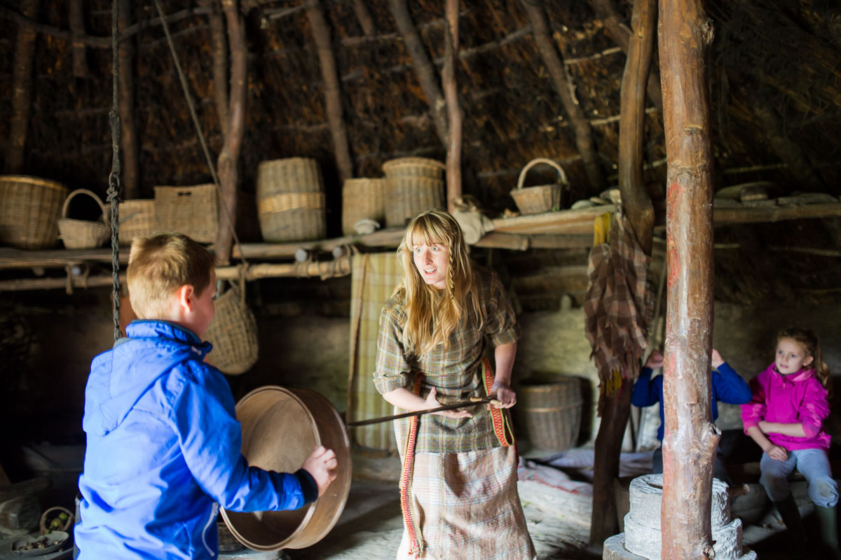 A costumed guide inside a roundhouse at Castell Henllys Iron Age Village is speaking to a young boy