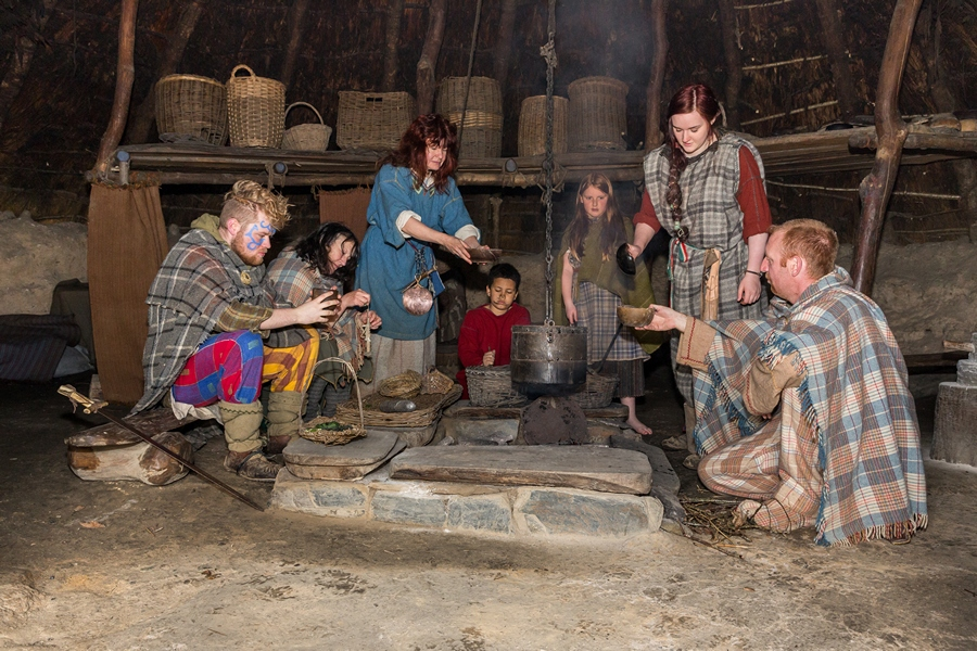 Seven members of an Iron Age family sit round the fire in an Iron Age roundhouse at Castell Henllys