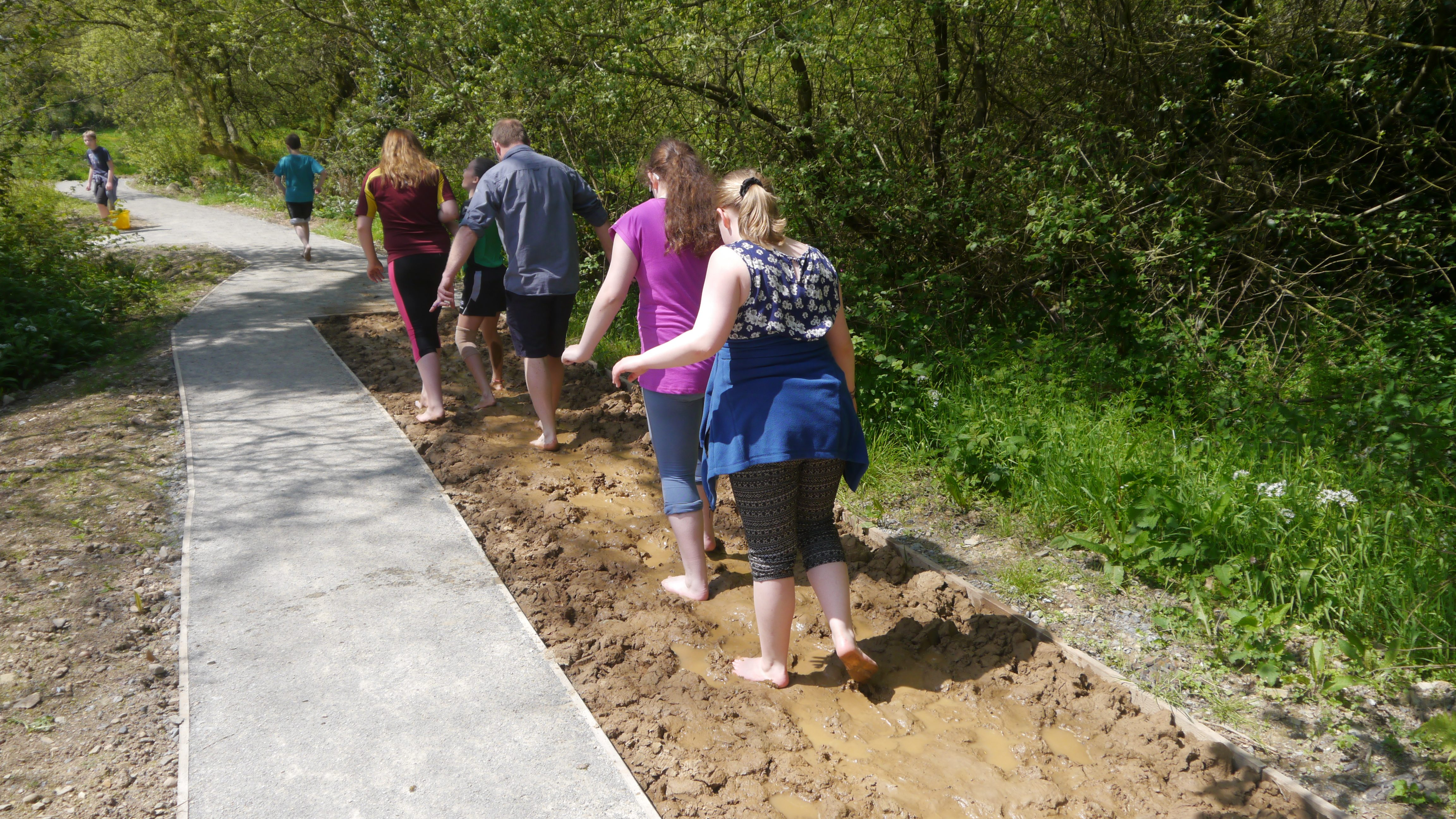 A group walking the barefoot on sand on Barefoot Trail at Castell Henllys