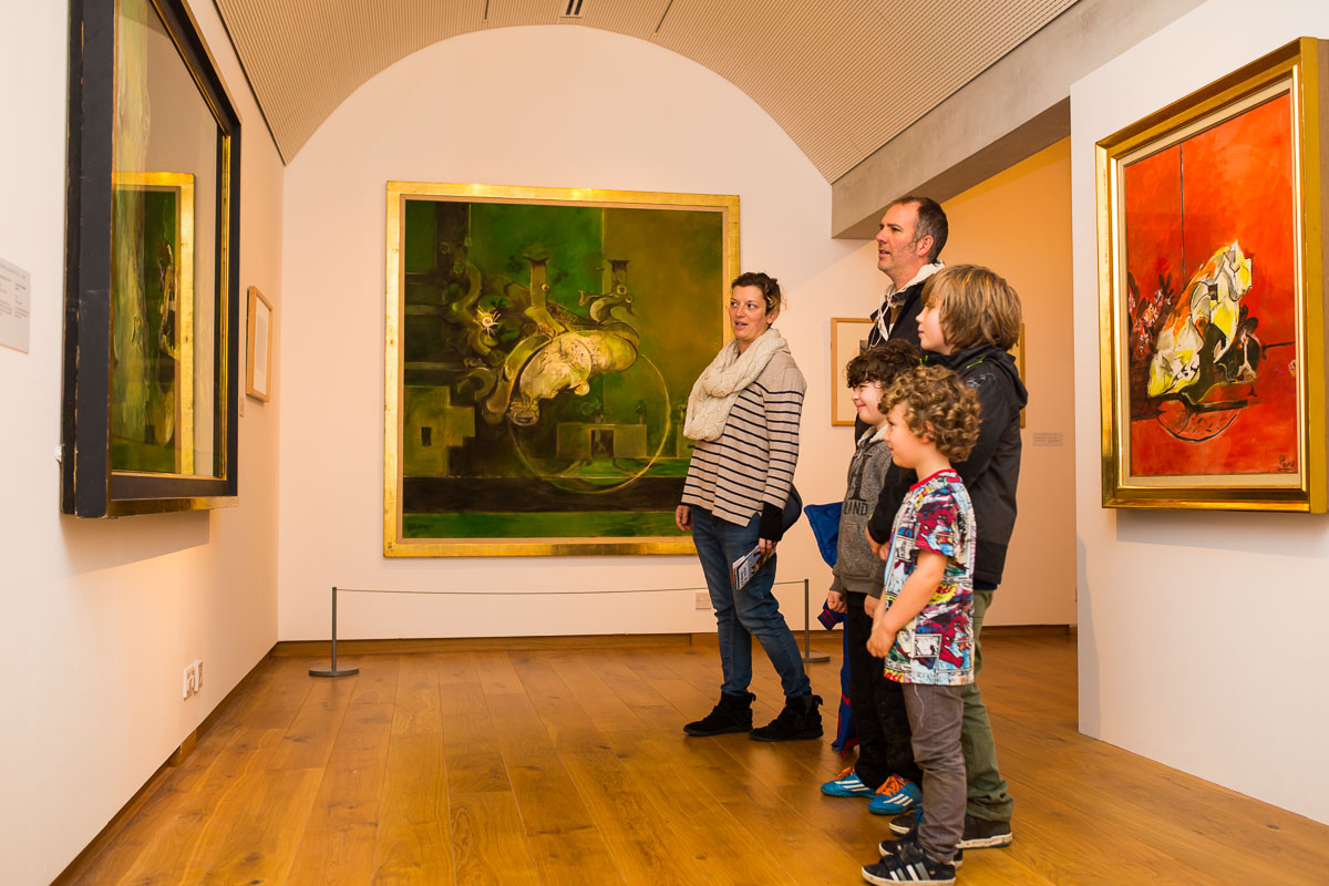 A family is viewing a Graham Sutherland painting