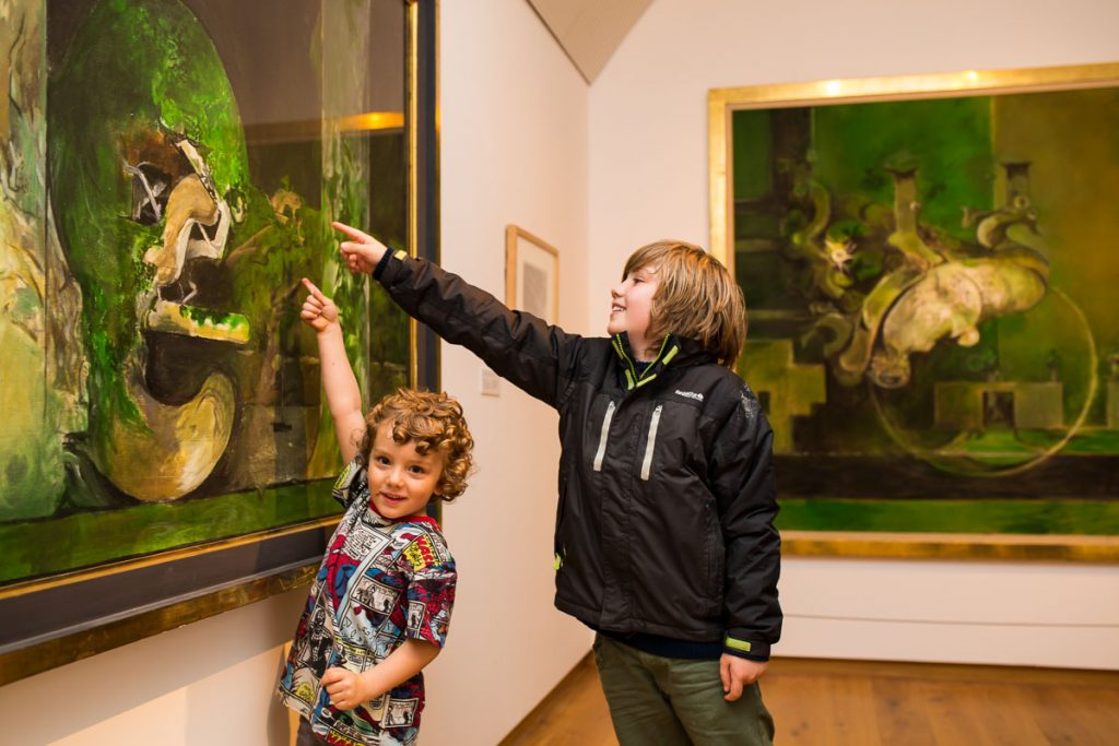 Two boys are pointing to a Graham Sutherland painting in the gallery at Oriel y Parc
