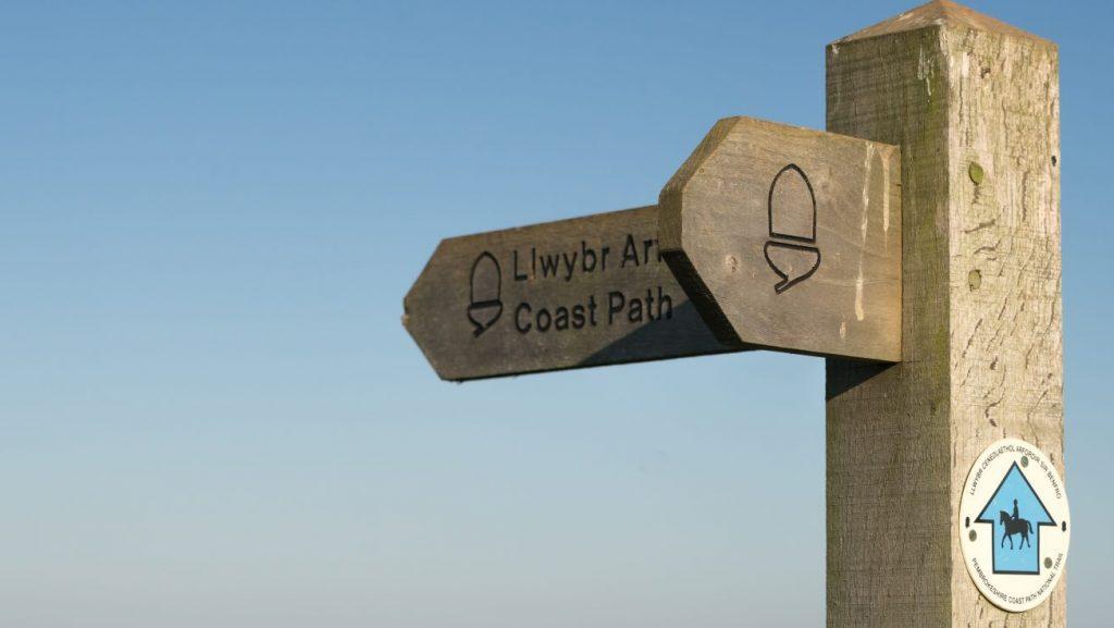 Wooden coast path direction sign, Pembrokeshire Coast Path, Pembrokeshire Coast National Park, Wales, UK
