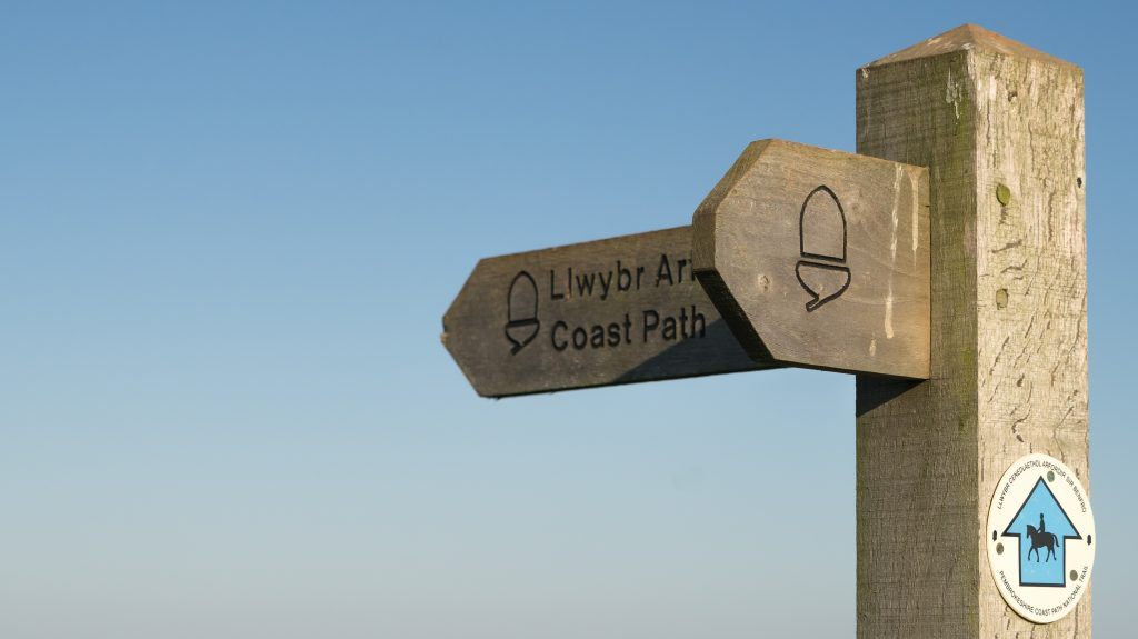 Wooden coast path direction sign, Pembrokeshire Coast Path, Pembrokeshire Coast National Park, Wales, UK