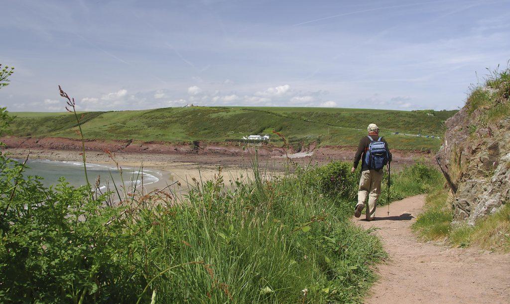 Walker on the Pembrokeshire Coast Path approaching Manorbier