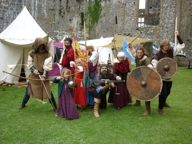 Group of people in medieval dress holding swords and shields