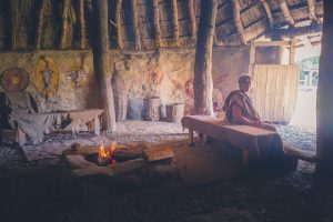 Woman dressed in Iron Age costume sitting inside roundhouse as campfire burns