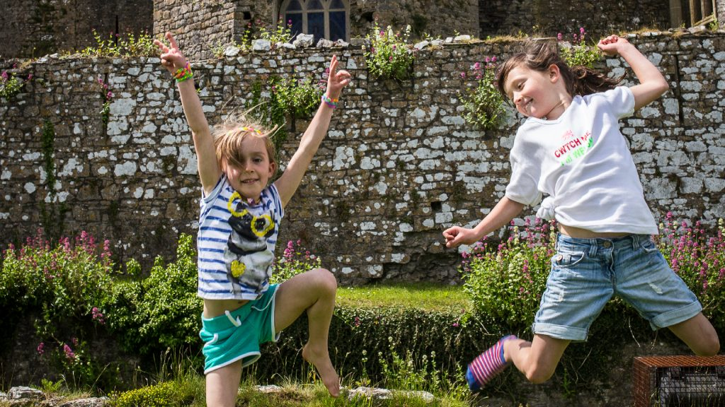 Two girls jumping in front of a stone castle