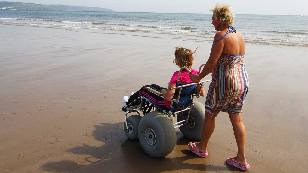 Adult woman pushing young woman in beach wheelchair along sandy beach on a sunny day