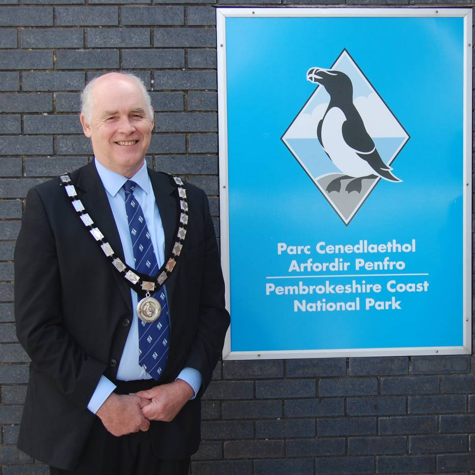 Man in suit wearing ceremonial tie standing alongside a sign that reads 'Pembrokeshire Coast National Park'